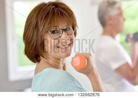 Senior people in gym lifting dumbbells