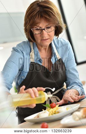 Senior woman in home kitchen preparing dish