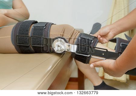 Orthopedist secures leg brace on knee knee brace support for leg or knee injury