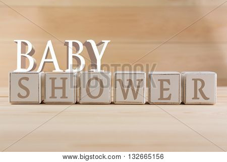 Educational cubes, on wooden background. Baby shower concept