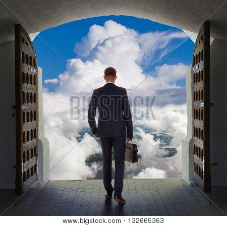 Young businessman is going to exit from gate and move toward the heavens.
