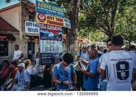 Dubrovnik Croatia - August 26 2015. Tourists stands next to signs with city tours information near the entrance to Old Town of Dubrovnik