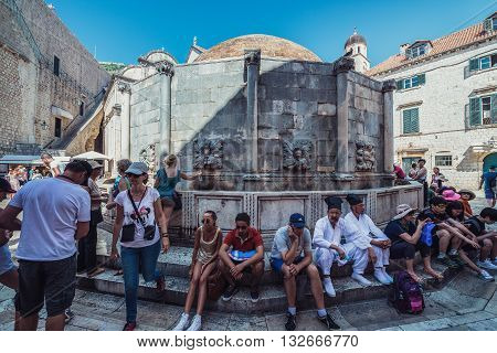 Dubrovnik Croatia - August 26 2015. Tourists sits next to most well-known fountain on the Old Town of Durbovnik city called Great Onofrio's Fountain