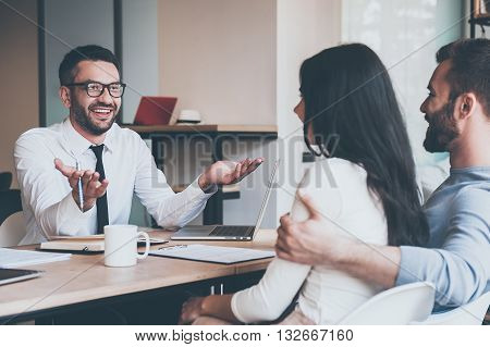 Sharing good news. Happy young couple bonding to each other and listening to cheerful mature man sitting at the desk in front of them and gesturing