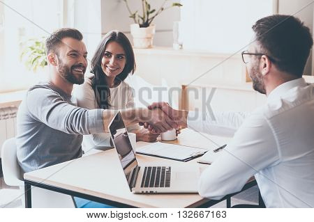Good deal! Cheerful young man bonding to his wife while shaking hand to man sitting in front of him at the desk