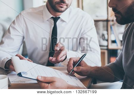 Signing contract. Close-up of confident young man signing some document while another man in shirt and tie sitting close to him and pointing document