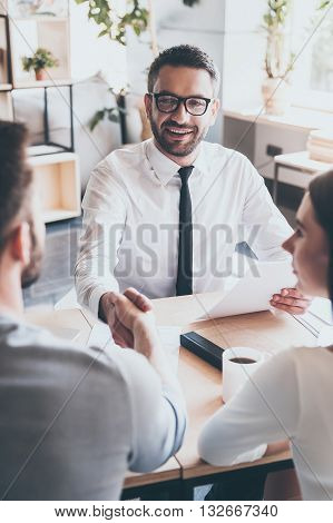 Congratulations! Two men sitting at the desk and shaking hands while young woman looking at them