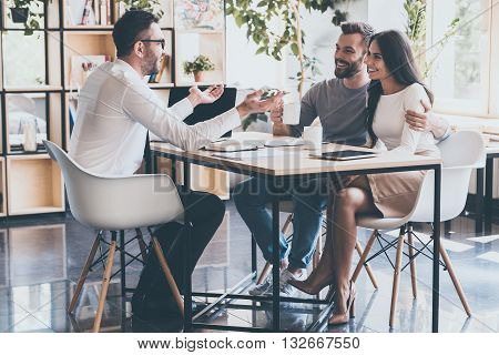 Good news for you! Cheerful young couple bonding to each other and listening to their financial advisor sitting at the desk in front of them