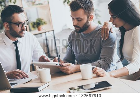 You should sign here. Confident young man signing some document while sitting together with his wife and man in shirt and tie