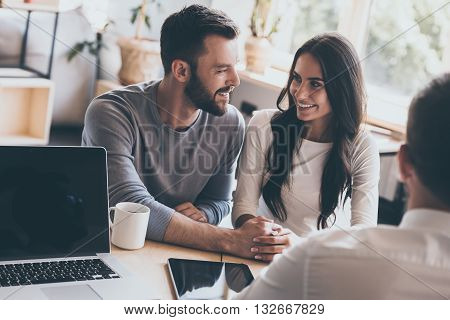 Now they feel happy. Happy young loving couple bonding to each other and looking at each other while sitting together with their financial advisor