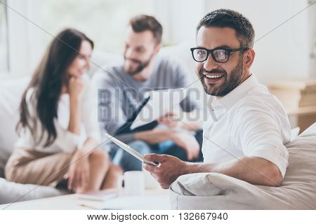 Confident sales manager. Cheerful mature man holding digital tablet and looking over shoulder while another man and woman sitting in the background