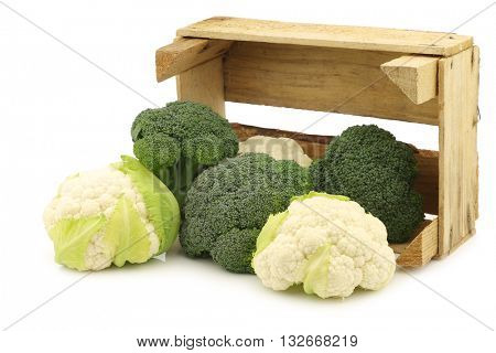 fresh small cauliflower and broccoli in a wooden crate on a white background