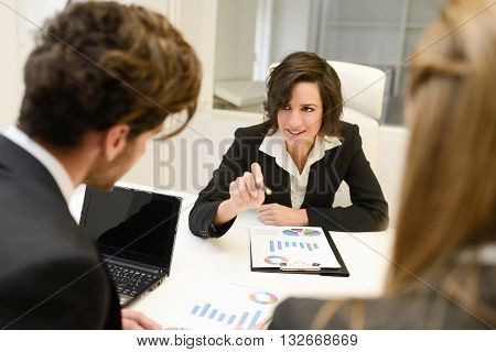 Image of business partners discussing documents and ideas at meeting. Woman leader wearing blazer