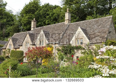 Traditional stone English cottages in Cotswolds village with colorful flowers and trees in bloom in front garden