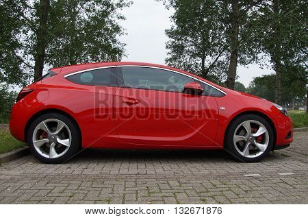 Almere, The Netherlands - May 29, 2016: Red Opel Astra GTC parked on a public parking lot in the city of Almere.