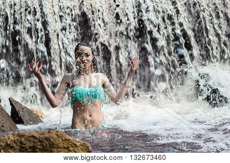 attractive woman splashes water on waterfall outdoors