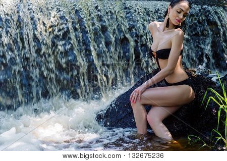 elegant woman in black swimsuit on background waterfall