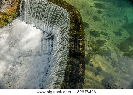 Semicircular dam with small lake that cause waterfall 01
