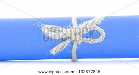 Handmade natural rope knot tied on blue paper roll isolated