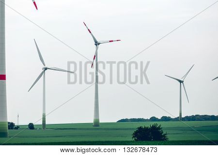 Metal Ecological windmills standing in a green field. Yard of windmill power generator under blue sky. Ecological power with windmill on the field.