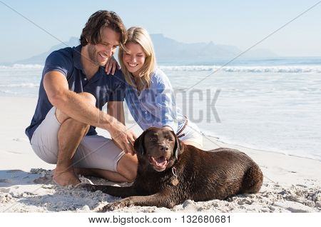Cheerful couple at beach playing with labrador retriever. Couple relaxing at beach with their pet. H