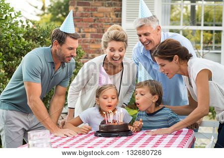 Happy generation family watching girl blowing out birthday candles at picnic table outside. Happy little girl celebrating birthday with family. Brother helping sister blow candles on her birthday.
