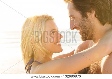 Attractive couple embracing on the beach on a sunny day. Young attractive couple in love. Loving couple embracing each other on the beach against ocean at sunset.