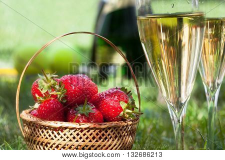 Strawberries and glasses with champagne on the grass