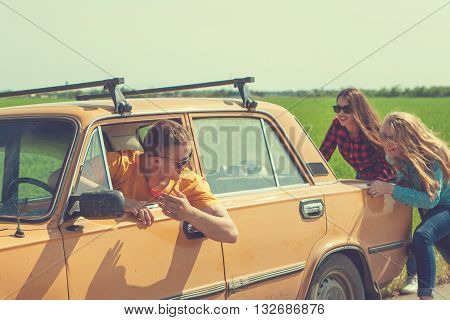 Young hipster friends on road trip on a summers day. Engine break down.Two girls pushing a vintage car while man is emboldening their.Travel adventure unforeseen teamwork funny concept