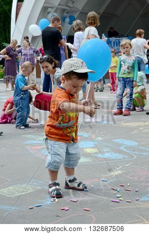 KHARKOV UKRAINE - 20 JUNE 2015: World Refugee Day observed in Kharkov Ukraine. A little boy with a blue baloon playing with colorful pieces of chalk.