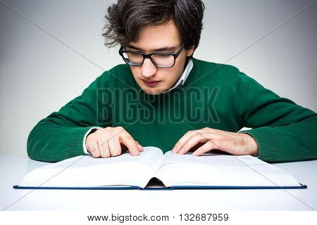 Front view of young man in green pullover sitting at white table and reading big book