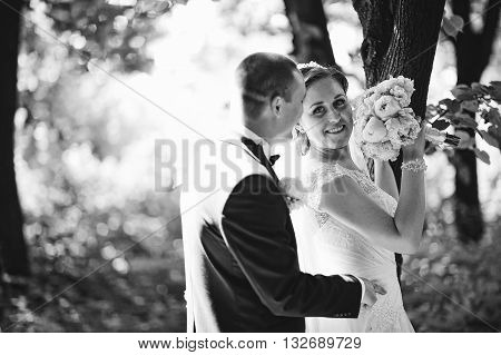 Fashionable Wedding Couple Stay Near Tree At Forest With Sun Lights. B&w Photo