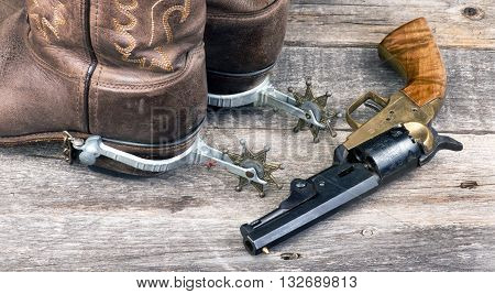 Old western pistol ,spurs and cowboy boots.
