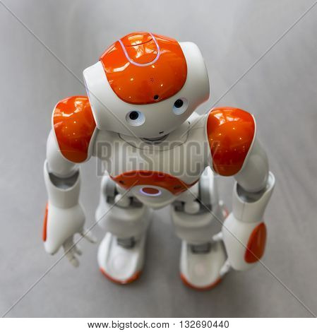 Sofia, Bulgaria - June 1, 2016: A small robot with human face and body - humanoid. Artificial Intelligence - AI. Orange robot.