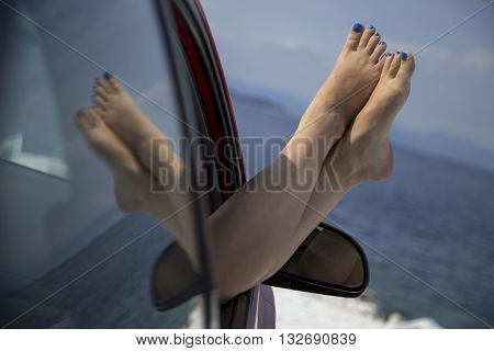 Barefoot female legs put outside of the car window with the seascape in the background