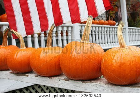 Close up of small pumpkins lined up on a porch railing with the American Flag in the background