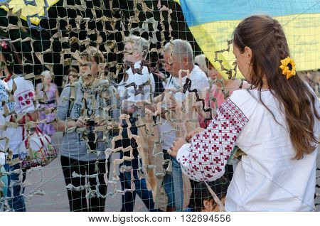 KHARKIV UKRAINE - 24 AUGUST 2015: A girl in national Ukrainian clothes vyshyvanka plaiting a camouflage net for the Ukrainian army fighting in the East of Ukraine