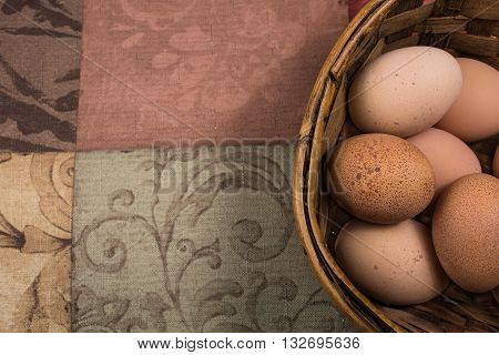 Fresh chicken eggs in a basket with tapestry to the side for copy space