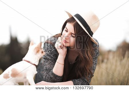 Stylish girl playing with chihuahua puppy outdoors. Wearing straw hat. Summer season.