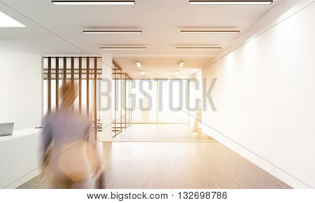 Side view of concrete office lobby with laptops on white reception desk window with New York city view and walking blurry businessman. Toned image 3D Rendering