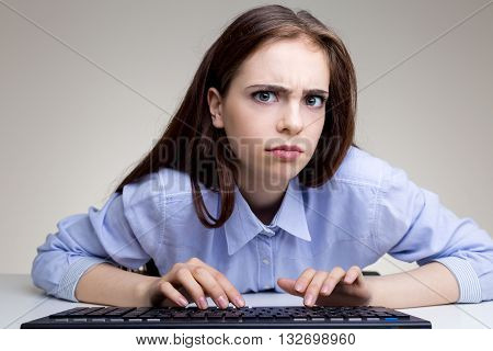 Frowning young woman using computer keyboard on grey office desktop