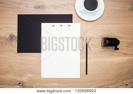 Top view of wooden tabletop with black and white paper sheets with pencil coffee cup and sharpener. Mock up