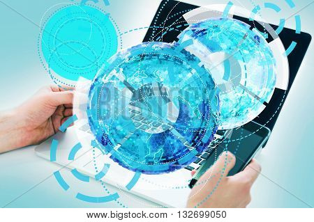 Technology concept with abstract circular digital pattern and businessman hands using laptop and smartphone on blue background