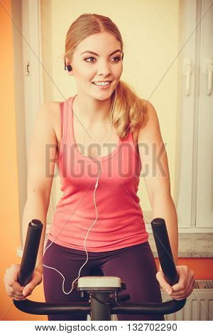 Active young woman working out on exercise bike stationary bicycle. Sporty girl training at home listening music. Fitness and weight loss concept. Instagram filtered.