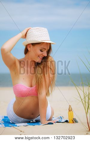 Sun protection concept. Attractive sexy long haired woman in straw hat lying on beach with sunscreen body lotion and sunglasses.