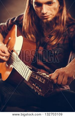 Music hobby concept. Young guitarist is tuning guitar. Man is very focused and touching the strings.