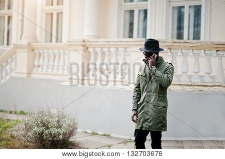 Fashion Portrait Of Black African American Man On Green Coat Cloak And Black Hat,talking On The Mobi