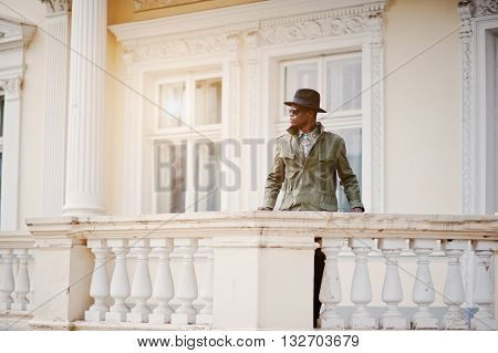 Fashion Portrait Of Black African American Man On Green Coat Cloak And Black Hat, Stay On The Balcon