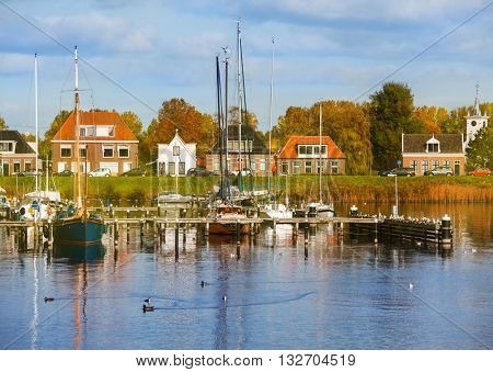 Typical Dutch countryside in autumn with yachts in the foreground