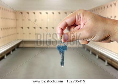 Male hand holding a key in an empty locker room